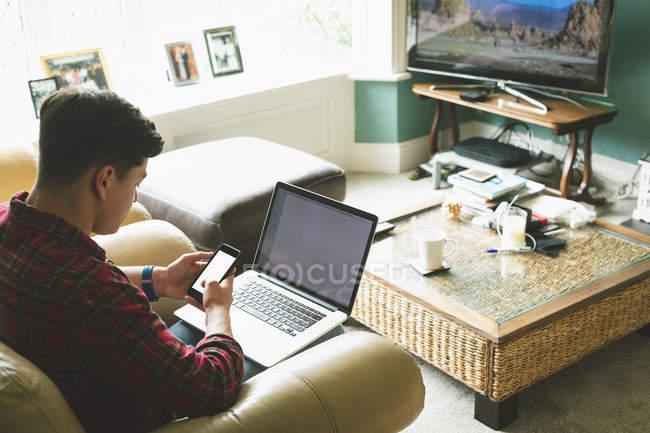 Hombre usando el ordenador portátil y el teléfono móvil en la sala de estar en casa . - foto de stock