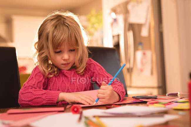 Adorable girl drawing on paper at home — Stock Photo