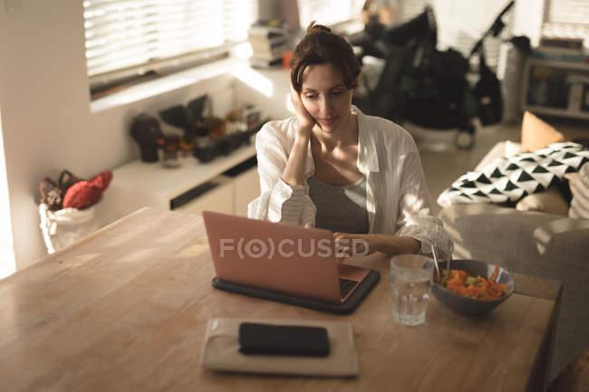 Junge Frau mit ihrem Laptop auf dem Tisch im heimischen Wohnzimmer — Stockfoto