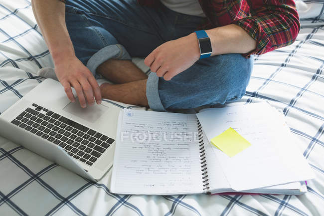 Low section of man using laptop at bed with notebook. — Stock Photo