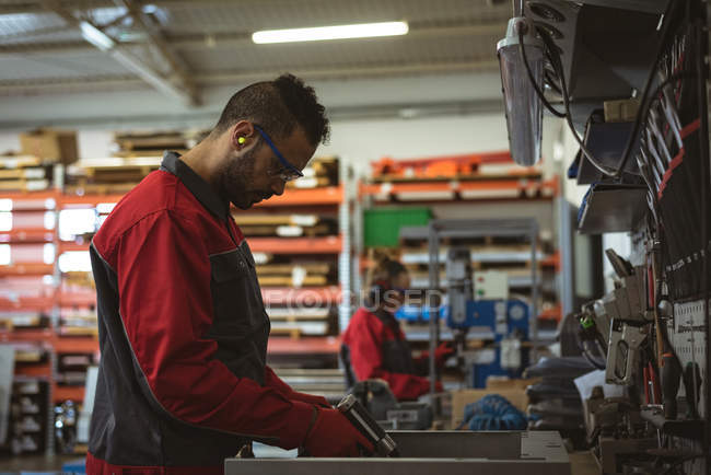 Trabajador masculino reparando una máquina con herramienta en fábrica - foto de stock