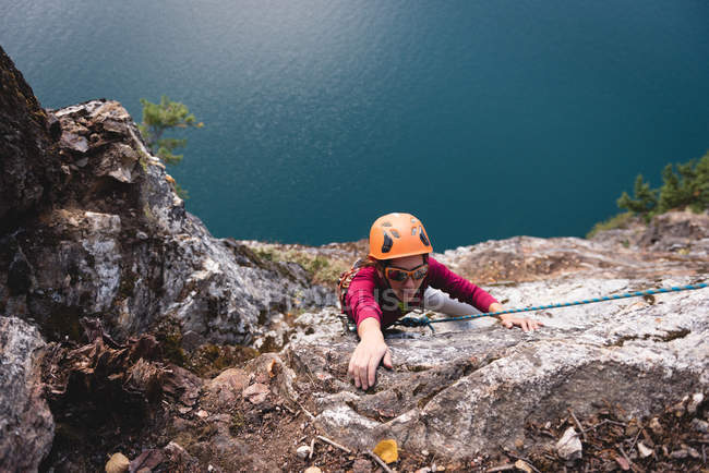 Female rock climber climbing the rocky mountain near lakeside — Stock Photo