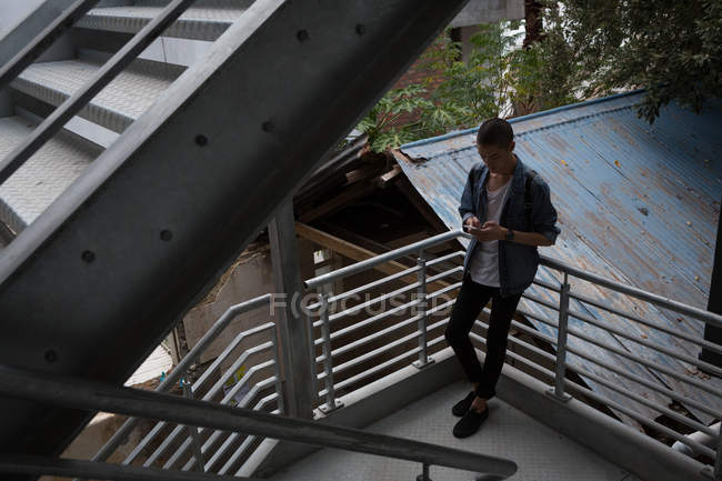 Young man using mobile phone in stairs — Stock Photo