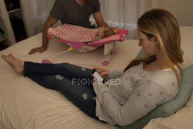 Матері, що використання мобільного телефону у спальні з родиною у фоновому режимі на дому — стокове фото