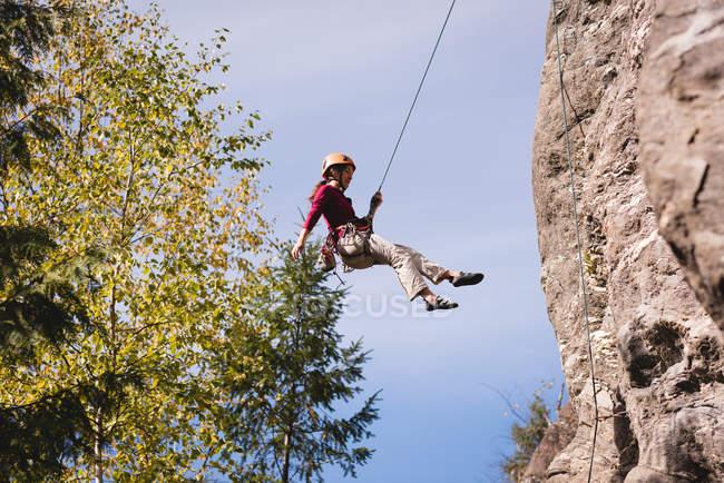 Mulher alpinista lutando até a montanha rochosa em um dia ensolarado — Fotografia de Stock
