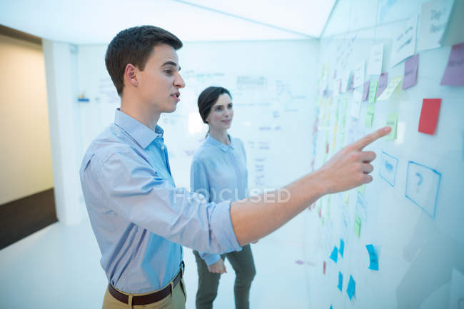 Male and female executives reading sticky notes in futuristic office — Stock Photo