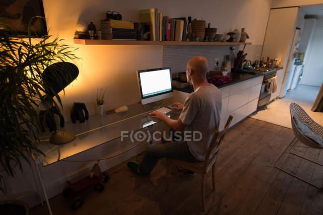 Homme travaillant sur un ordinateur personnel à la maison . — Photo de stock