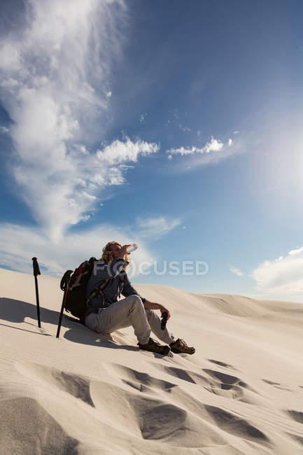Male hiker looking through binocular on sand at desert — Stock Photo