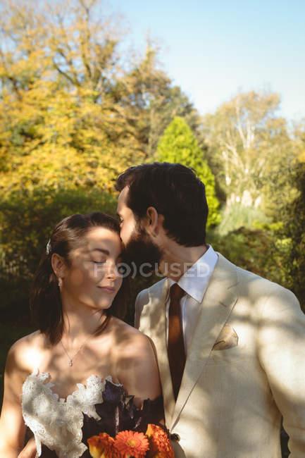 Groom baisers sur les mariées front dans le jardin — Photo de stock