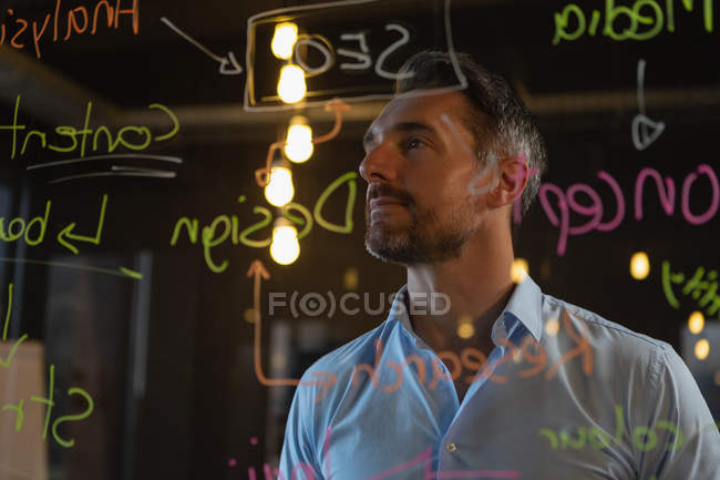 Thoughtful male executive reading notes on glass wall in office. — Stock Photo