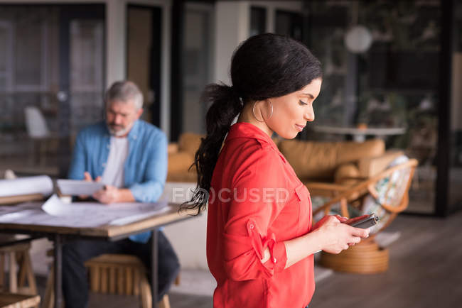 Smiling office executive using mobile phone at creative office — Stock Photo