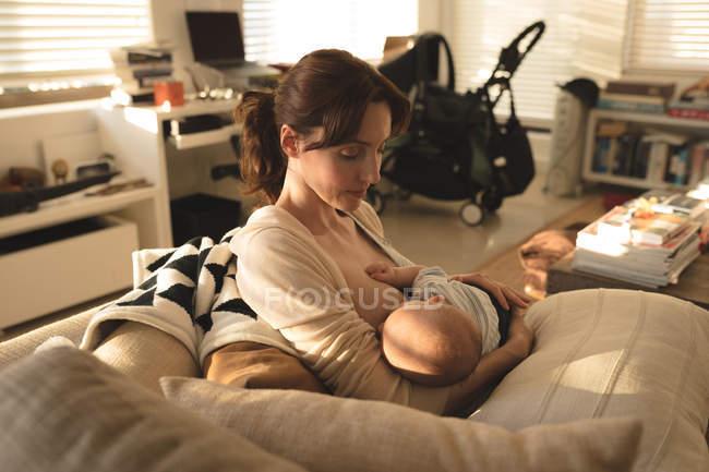Молодая мама, сидя на диване грудного вскармливания ребенка в гостиной дома — стоковое фото