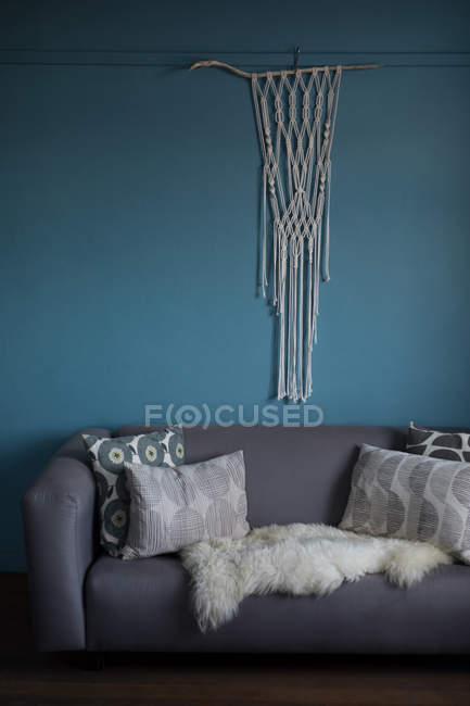 Thread curtain hanging against blue wall in living room — Stock Photo