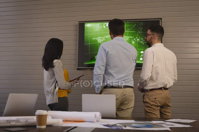 Rear view of business people discussing graph on screen in conference room at office. — Stock Photo