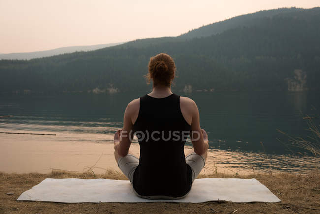 Back view of fit man sitting in meditating posture on an open ground — Stock Photo