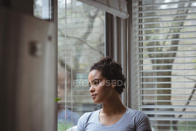 Thoughtful woman looking through the window at home — Stock Photo