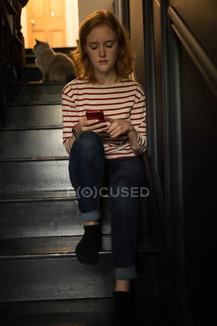 Молодая женщина сидит на лестнице, используя свой мобильный телефон дома — стоковое фото
