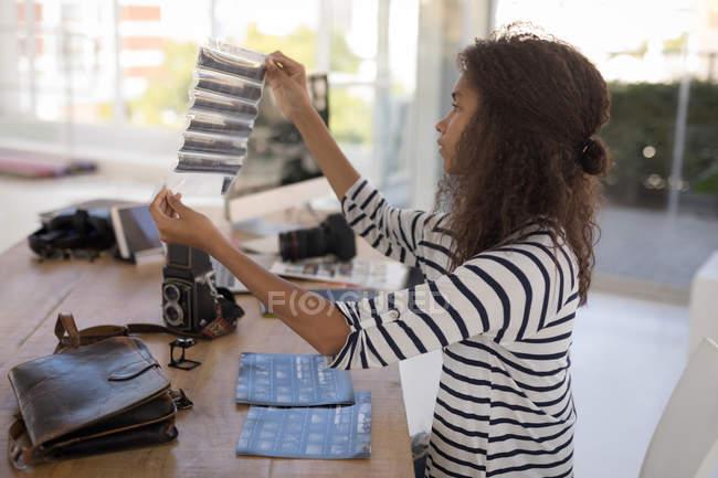 Фотограф перевірка фотонегативів бюро в фото-студії — стокове фото