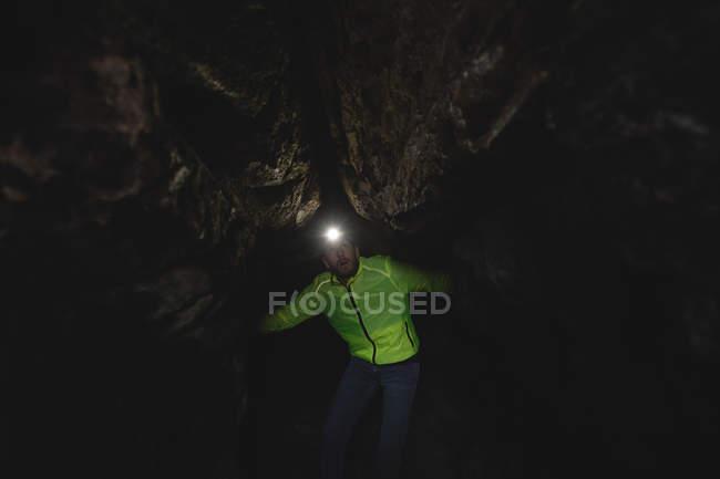 Randonneur explorant la grotte sombre — Photo de stock