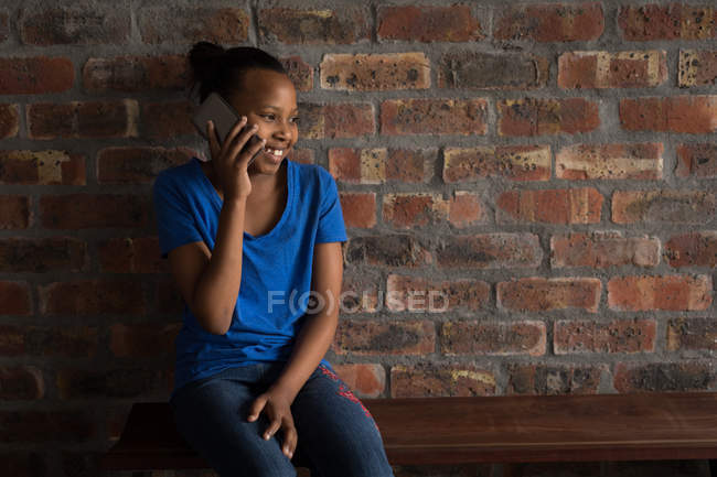 Happy girl talking on mobile phone in office. — Stock Photo