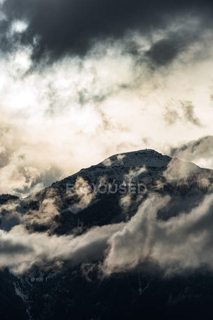 Mountain top surrounded with clouds at evening — Stock Photo