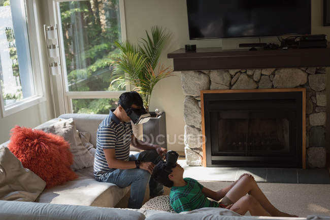 Father and son using virtual reality headset in living room at home — Stock Photo