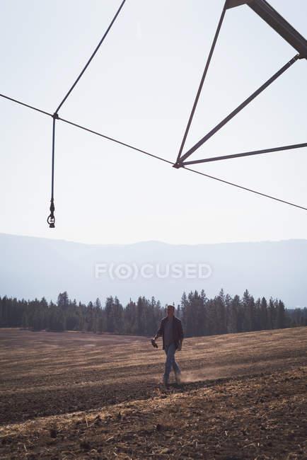 Agricultor caminhando no campo em um dia ensolarado — Fotografia de Stock