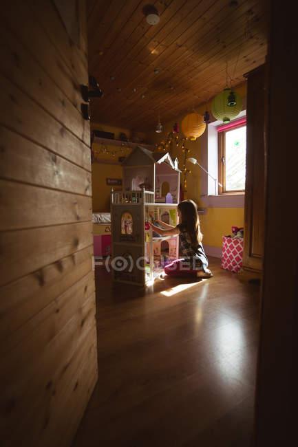 Menina brincando com casa de bonecas no quarto em casa — Fotografia de Stock