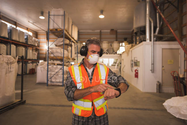 Man in protective workwear using smartwatch in factory — Stock Photo