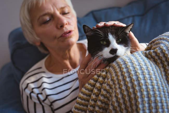 Nahaufnahme einer Seniorin, die zu Hause auf dem Sofa sitzt und ihre Katze streichelt — Stockfoto