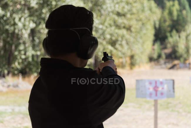Vista traseira do homem apontando a arma no alvo no tiro ao alvo — Fotografia de Stock