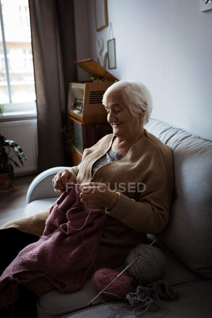 Senior woman knitting wool in living room at home — Stock Photo