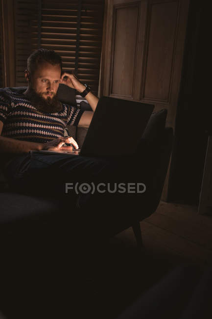 Close-up of man in dark room sitting on sofa using his laptop at home — Stock Photo