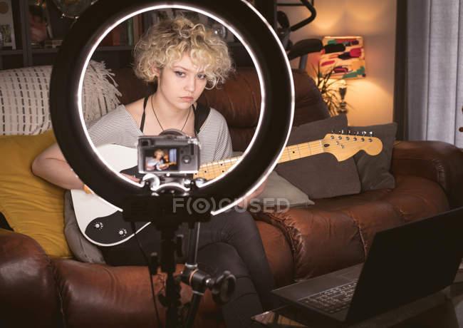 Blogueuse jouant de la guitare dans le salon à la maison — Photo de stock