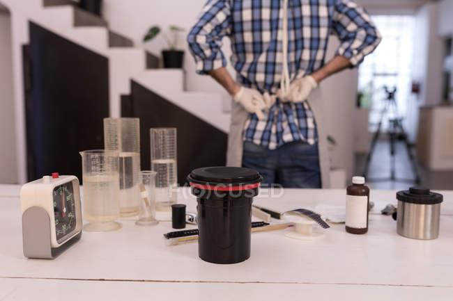Bouchon d'objectif de caméra avec produit chimique sur une table en studio photo — Photo de stock