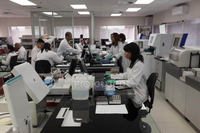 Équipe de techniciens de laboratoire travaillant ensemble dans une banque de sang — Photo de stock