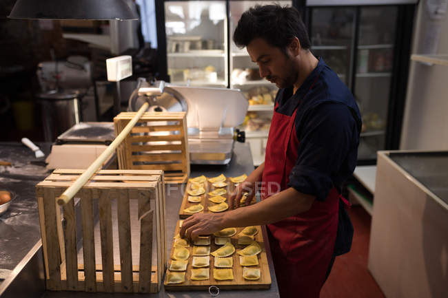 Мужчина пекарь готовит макароны из агнолотти в пекарне — стоковое фото