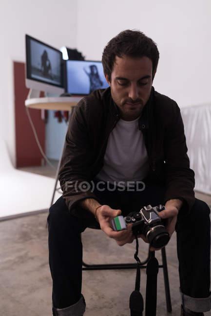 Чоловічий фотограф проведенні рулону плівки і камери в фото-студії — стокове фото