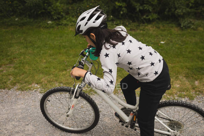 Young girl riding bicycle on street — Stock Photo