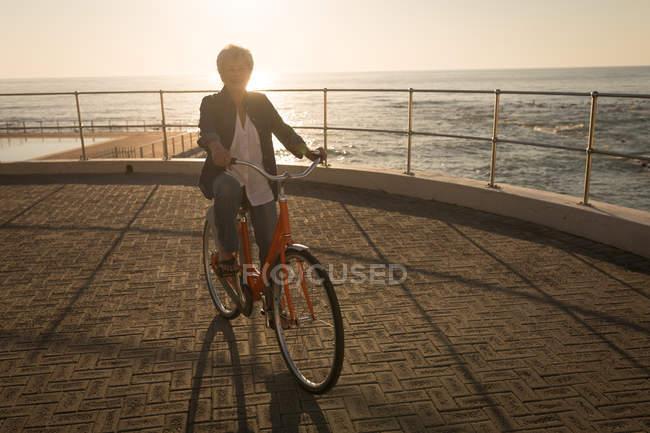 Старшие женщины езда велосипедов на набережной в Солнечный день — стоковое фото