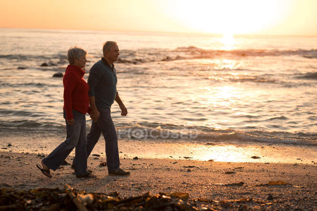 Couple sénior marchant sur la plage au coucher du soleil — Photo de stock