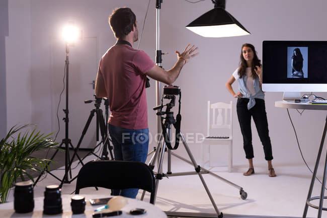 Fotógrafo masculino e modelo feminino interagindo uns com os outros no estúdio de fotografia — Fotografia de Stock