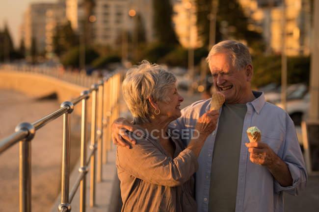 Happy senior couple having ice cream at promenade — Stock Photo