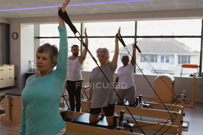 Gruppo di donne anziane che fanno esercizio di stretching nel centro yoga — Foto stock