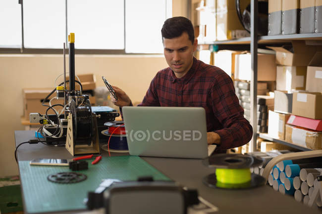 Mechanic using laptop on desk in workshop — Stock Photo