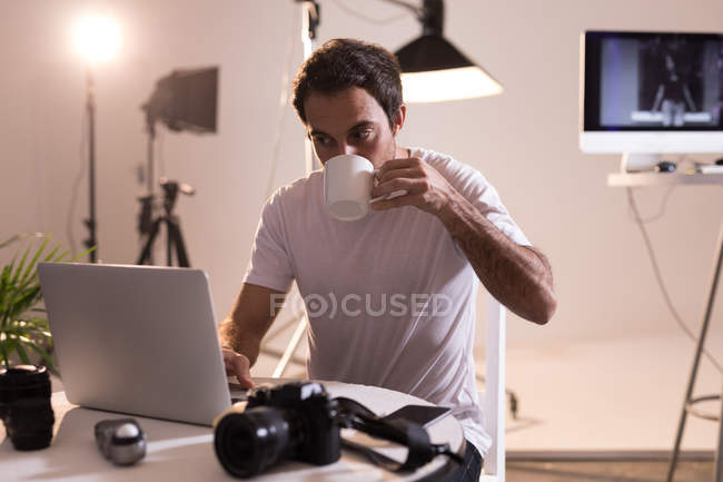 Male photographer having coffee while using laptop in photo studio — Stock Photo