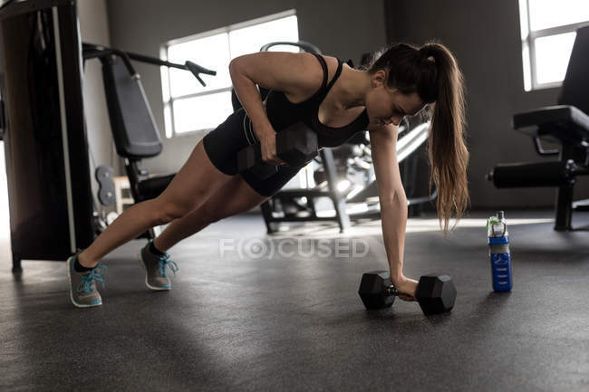 Beautiful woman doing push ups on dumbbells in fitness studio — Stock Photo