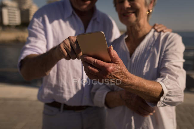 Senior couple using mobile phone at promenade — Stock Photo