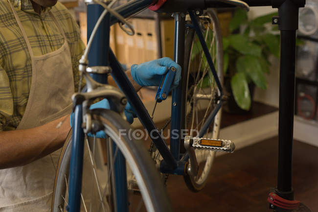 Mid section of mechanic fixing bicycle brake wire in workshop — Stock Photo
