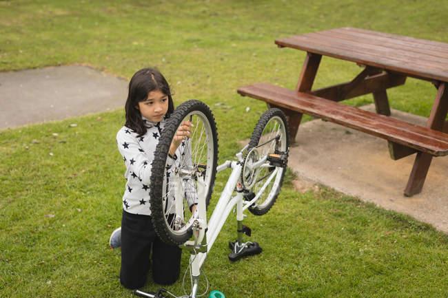 Молодая девушка чинит велосипед в саду — стоковое фото